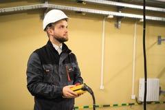 Работник техника нося в равномерных пользах удаленных для крана силы вагонетки подкрановой балки поднимаясь Человек контролирует  стоковая фотография