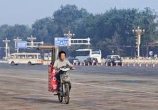 Работник транспортирует крены марли на его электрическом велосипеде, Пекине, Китае Стоковые Изображения