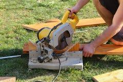 Работник увидел что древесина с отбивной котлетой увидело стоковая фотография rf