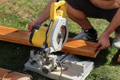 Работник увидел что древесина с отбивной котлетой увидело стоковая фотография