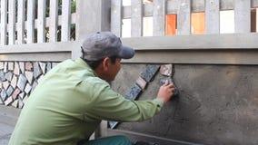 Работник устанавливает поверхность каменной стены с цементом видеоматериал
