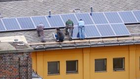 работник устанавливая квартиру верхней части крыши панели солнечных батарей сток-видео
