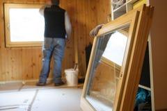 Работник устанавливая новые деревянные окна стоковая фотография