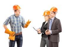 Работник физического труда имея переговор с архитекторами стоковые фотографии rf