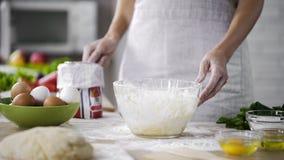 Работник хлебопекарни держа сетку муки для добавлять в стеклянный шар, рецепт пиццы наклоняет стоковое изображение rf