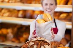 Работник хлебопекарни держа сумку хлеба Стоковая Фотография