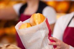 Работник хлебопекарни держа сумку хлебов Стоковое Изображение RF
