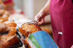 Работник хлебопекарни держа сумку хлебов Стоковая Фотография RF