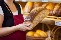 Работник хлебопекарни держа хлебец хлеба шкафом дисплея Стоковое Фото