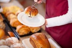 Работник хлебопекарни держа хлеб в плите Стоковая Фотография