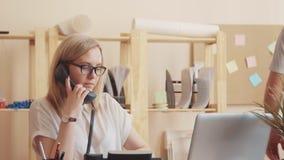 Работник центра телефонного обслуживания говорит по телефону и пишущ текст на бумаге, коллега проходит мимо, дает ее видеоматериал