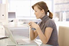 работник чая офиса привлекательного стола выпивая Стоковое фото RF