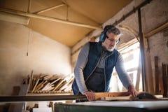 Работник человека в мастерской плотничества, работая с древесиной Стоковые Изображения