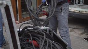Работник человека принимает вне кабели с черной пропиткой от фургона и кладет их в случай шкафа акции видеоматериалы