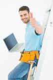 Работник Construciton показывать большие пальцы руки вверх пока полагающся на лестнице Стоковая Фотография