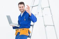 Работник Construciton показывать О'КЕЫ пока полагающся на лестнице Стоковое Изображение