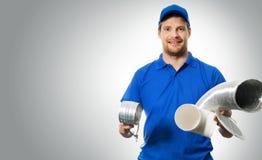 Работник Hvac с оборудованием системы вентиляции в руках на сером цвете Стоковое фото RF