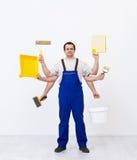 Работник Multitasking готовый для того чтобы покрасить комнату стоковые фотографии rf