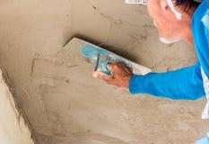 Работник plasterize бетон потолка и стены Стоковые Фото