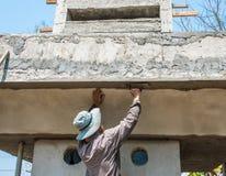 Работник plasterize бетон потолка и стены Стоковая Фотография