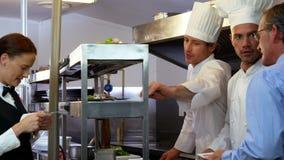Работодатель смотря шеф-поваров принимая заказы сток-видео
