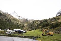 Работы машинного оборудования затяжелителя или backhoe экскаватора ждать outdoors на otztal горных вершинах стоковое фото