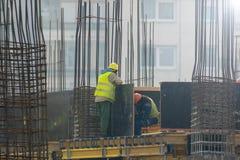 2 работы работают на баре подкрепления на строительной площадке Стоковое фото RF