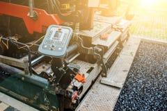 Работы ремонта приведения в исполнение: заасфальтируйте ролик штабелируя и отжимая горячее положение асфальта Машина ремонтируя д стоковая фотография