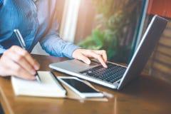 Работы руки женщины в портативном компьютере и пишут на блокноте i стоковые фотографии rf