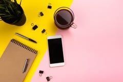 Рабочая зона стола офиса - плоский положенный взгляд сверху рабочей зоны с белыми пустыми тетрадью, наушником, кофейной чашкой и  стоковые фото