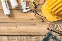 Рабочее место архитектора Запроектируйте светокопии конструкции и инструменты инженерства на деревянном столе, копируют космос стоковое фото
