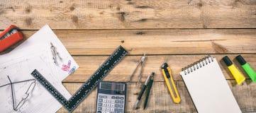 Рабочее место архитектора Запроектируйте светокопии конструкции и инструменты инженерства на деревянном столе, копируют космос стоковые фото