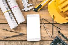 Рабочее место архитектора Smartphone с белым, пустым экраном, светокопиями конструкции проекта и инструментами инженерства на дер стоковые изображения rf