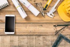 Рабочее место архитектора Smartphone с черными пустым экраном, светокопиями конструкции проекта и инструментами инженерства на де стоковые фото