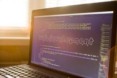 Рабочее место веб-разработчик в светах захода солнца Искусство ASCII фразы развития сети внутри реального кода HTML Стоковое Изображение RF