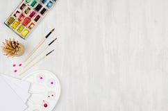 Рабочее место для чертежей - краски акварели, палитра, щетки, покрасили карандаши на белой деревянной доске, взгляд сверху, космо Стоковые Изображения RF