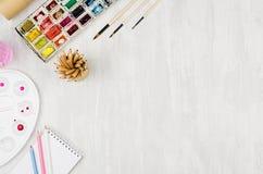 Рабочее место для чертежей - краски акварели, палитра, щетки, покрасили карандаши на белой деревянной доске, взгляд сверху, космо Стоковые Изображения