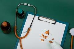 Рабочее место доктора - стетоскоп, таблетки, медицинские бутылки и пустая доска сзажимом для бумаги на предпосылке зеленой книги стоковые фото