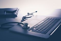 Рабочее место доктора с компьтер-книжкой и стетоскопом и тетрадью на белой таблице Стоковое Изображение
