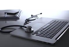 Рабочее место доктора с компьтер-книжкой и стетоскопом и тетрадью на белой таблице Стоковая Фотография RF
