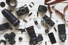 Рабочее место, камера, объективы и аксессуары фотографа на белой деревянной предпосылке Взгляд сверху стоковое фото