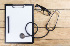 Рабочее место доктора Ручка, стетоскоп, доска сзажимом для бумаги на деревянной предпосылке стола Взгляд сверху Стоковые Изображения