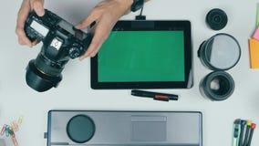 Рабочее место от выше Непознаваемый фотограф работая с его камерой, таблетка, карта памяти Взгляд сверху, greenscreen дальше видеоматериал