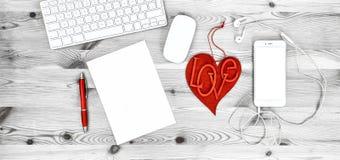 Рабочее место офиса с красным сердцем, клавиатурой, телефоном, наушниками Стоковые Фотографии RF