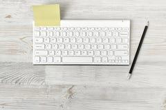Рабочее место офиса с клавиатурой, карандашем и желтым стикером Стоковое фото RF
