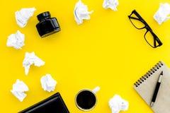 Рабочее место писателя с инструментами для работы на желтом модель-макете взгляд сверху предпосылки таблицы стоковое фото