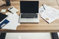 Рабочее место с компьтер-книжкой и документами стоковое изображение