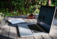 Рабочее место с компьтер-книжкой на террасе, тетрадью с аналитическими диаграммами и баком цветков Стоковые Изображения RF