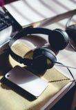 Рабочее место с сотовым телефоном, головным телефоном, клавиатурой и пустой книгой w Стоковое Изображение RF
