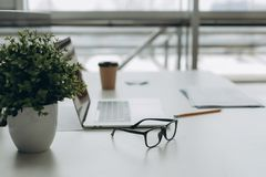 Рабочее место с таблицей работы ноутбука тетради удобной в окнах и виде на город офиса стоковые изображения